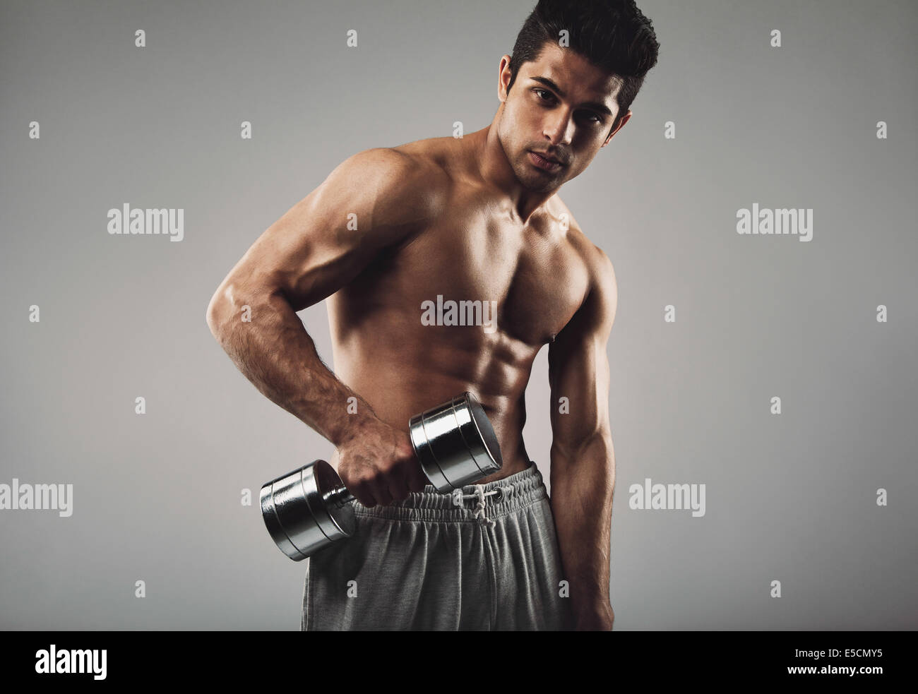Portrait of hispanic young man working out with heavy dumbbell on grey background. Shirtless muscular man doing - Stock Image