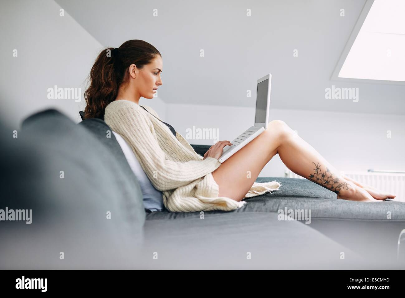 Side view of young lady sitting on sofa using laptop. Caucasian female model on couch surfing internet on laptop - Stock Image