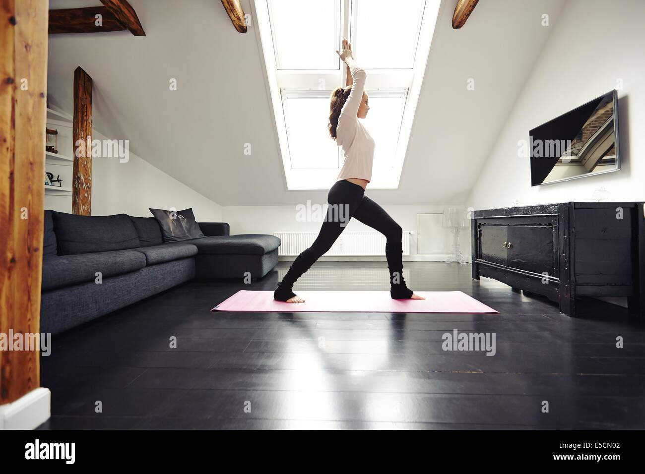 Fit young woman doing yoga at home. Healthy female model exercising in living home. - Stock Image