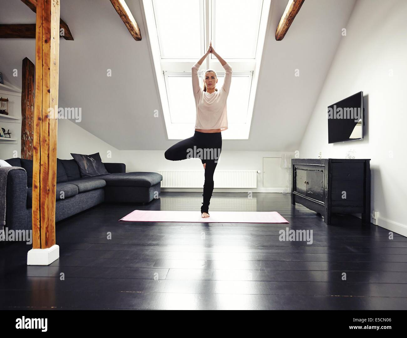 Full length image of fit young woman standing on one leg and meditating in her living room. Caucasian female doing - Stock Image