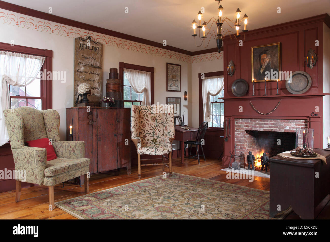 a formal living room with fireplace and two wing chairs white walls