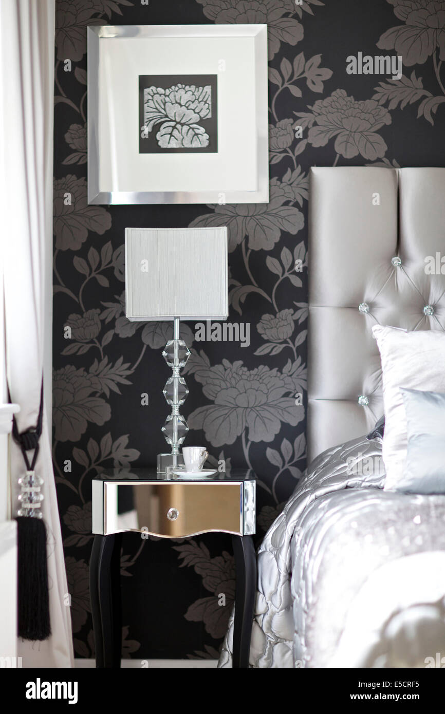 Mirrored bedside table in room with floral wallpaper and buttoned headboard, British home - Stock Image
