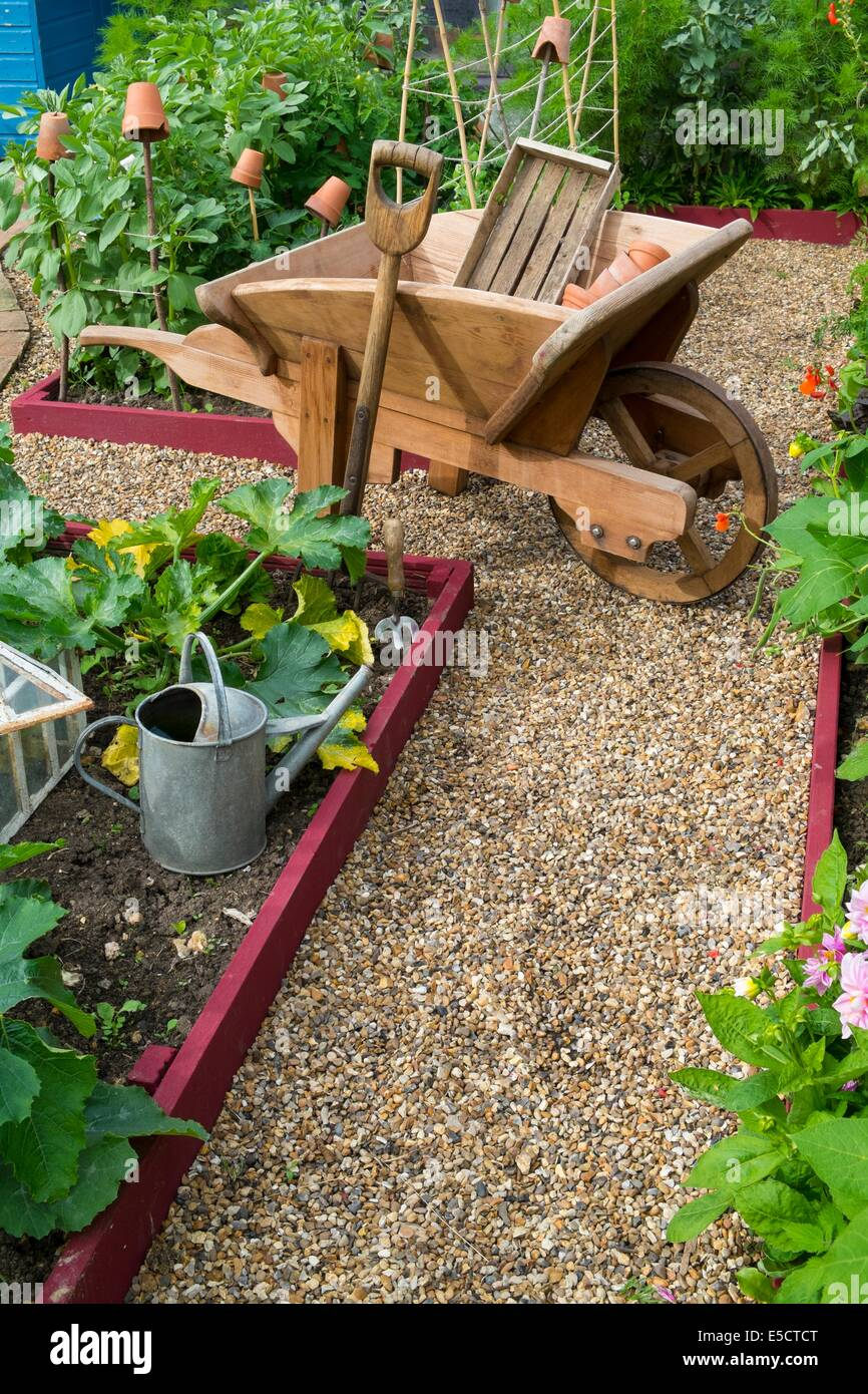 View of small raised bed crops with summer crops and traditional wooden wheelbarrow, England July. - Stock Image