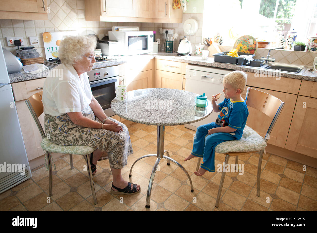 Grandmother sitting at the table with her grandson (aged 3) while he drinks a cup of milk and eats a biscuit, United - Stock Image