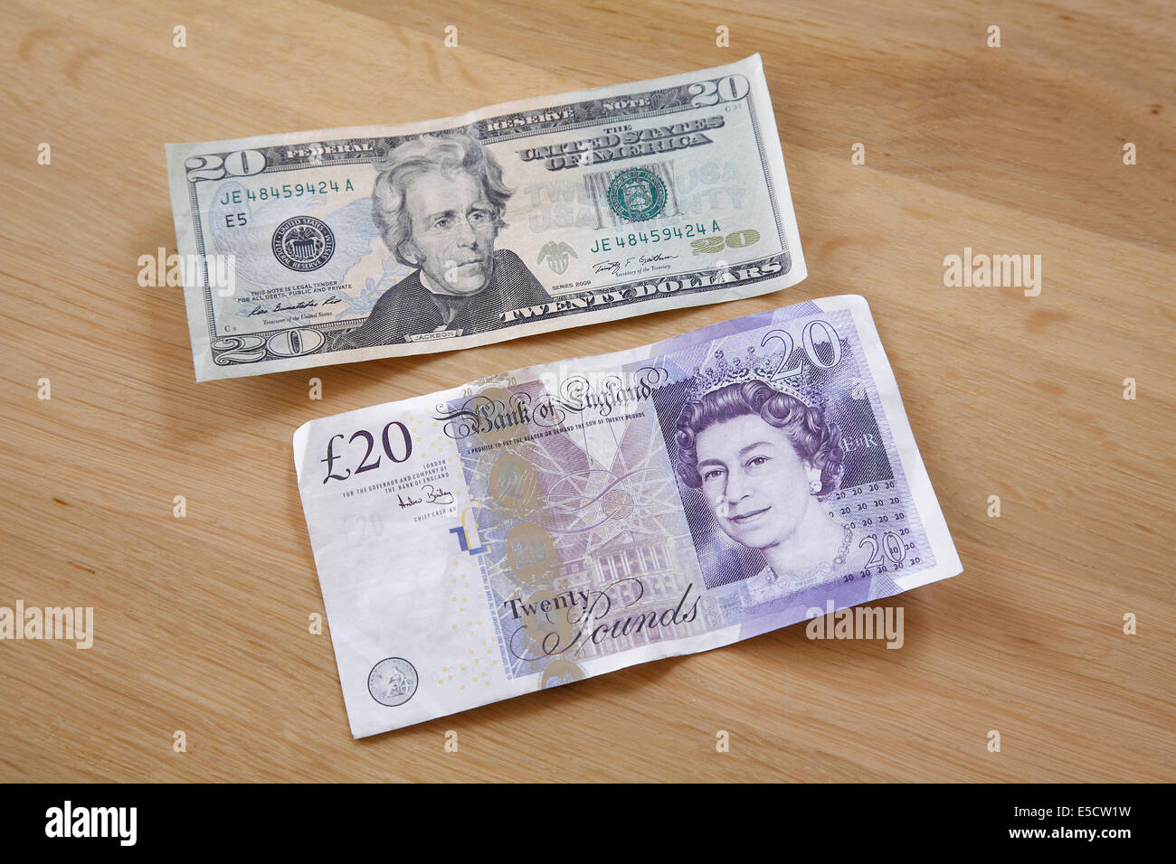 A 20 pound note and 20 dollar bill on a table. - Stock Image