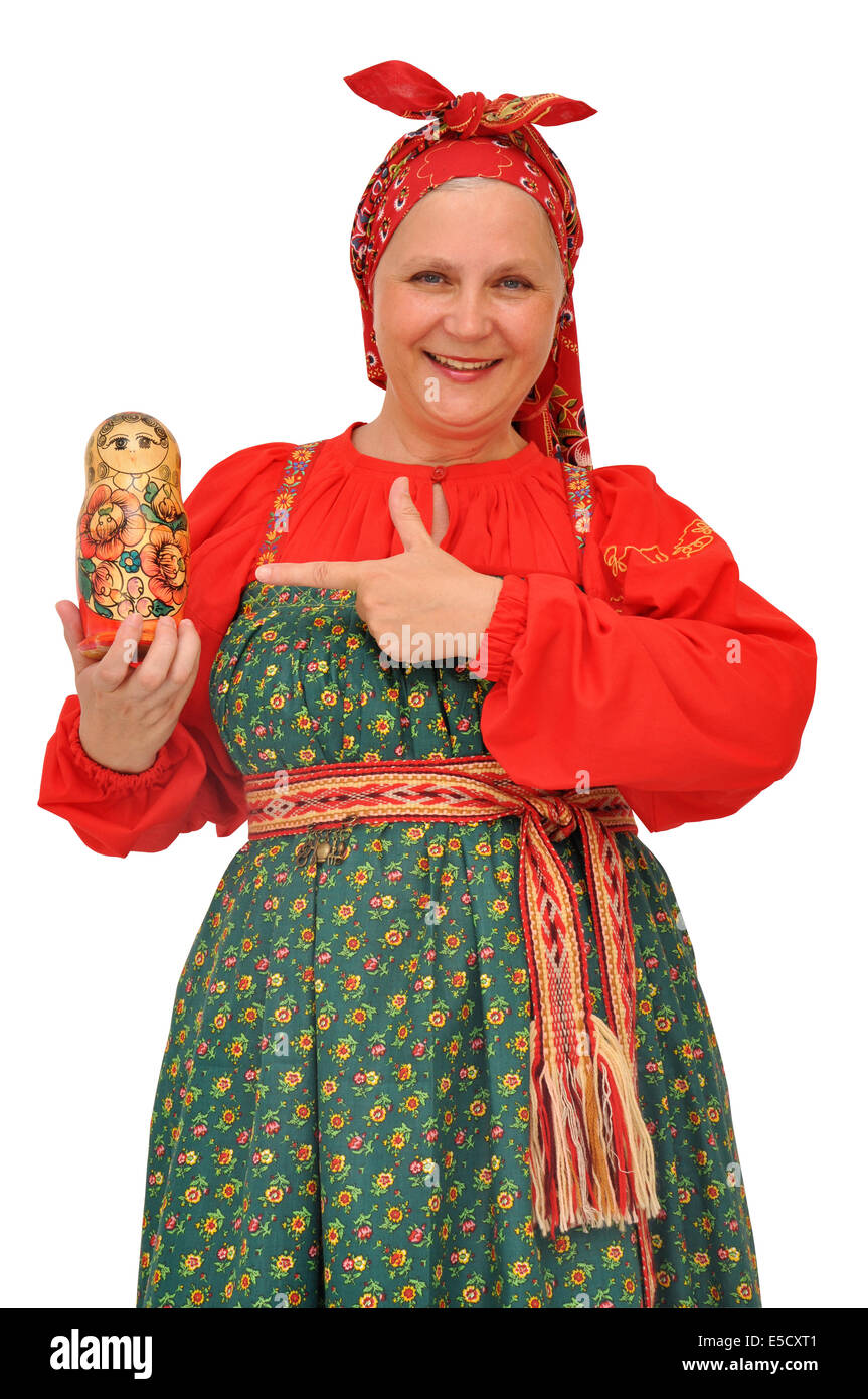 Joyful mature woman in bright traditional costume pointing finger at a nesting doll - Stock Image