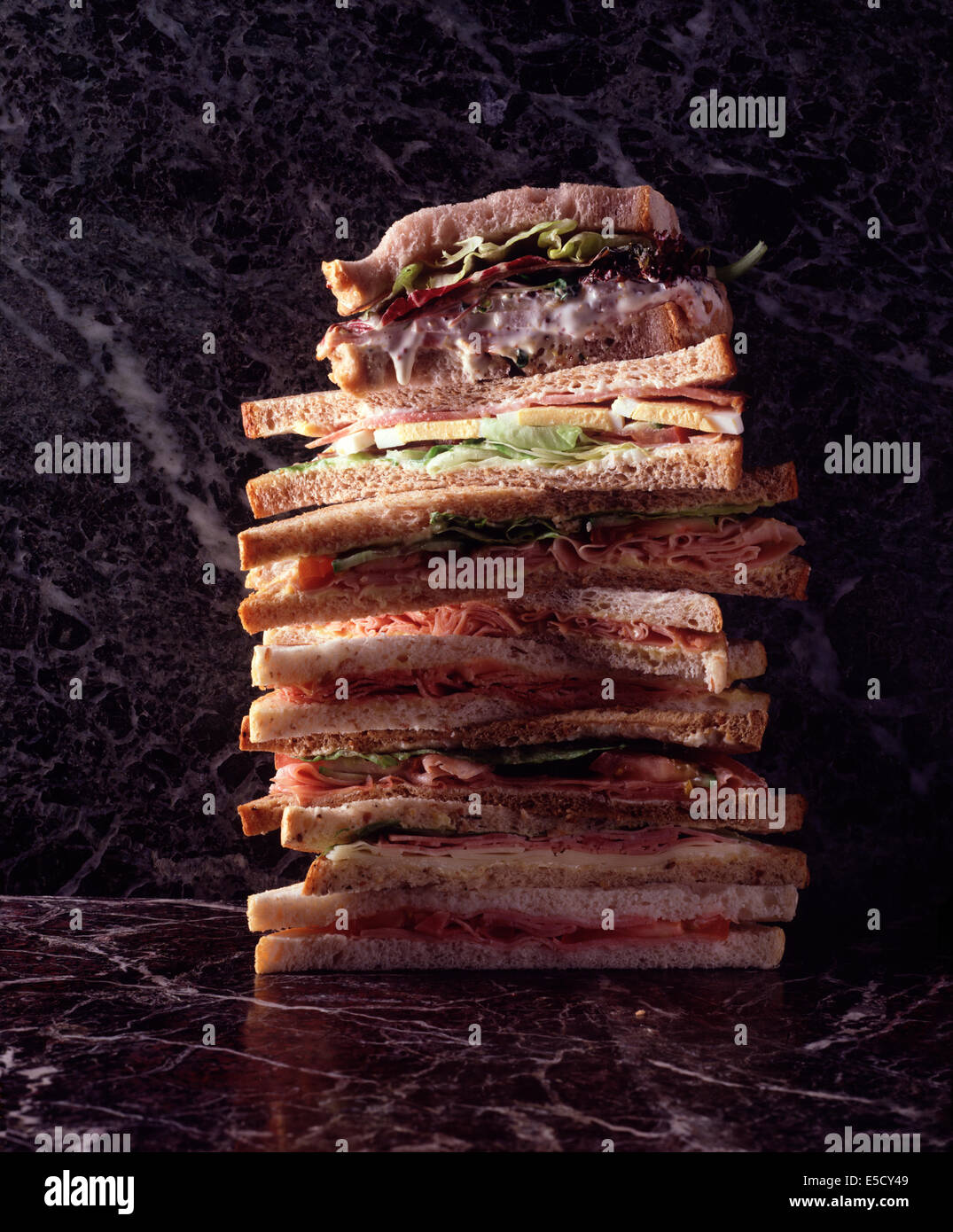 A stack of sandwiches one on top of the other, against a green and purple marble background. - Stock Image