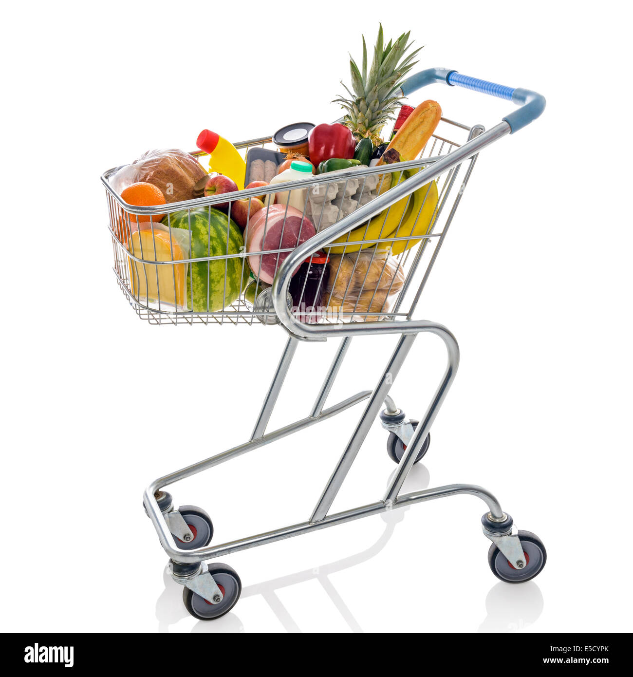Shopping trolley full of fresh groceries isolated on a white background. - Stock Image