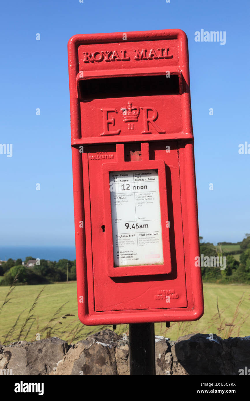 Newly painted wonky red Royal Mail postbox leaning sideways against blue sky. UK, - Stock Image