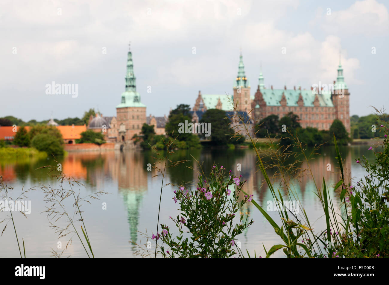 Frederiksborg Castle in Hillerød, North Zealand, seen from the other bank of the Castle Lake. Great willow-herb Stock Photo