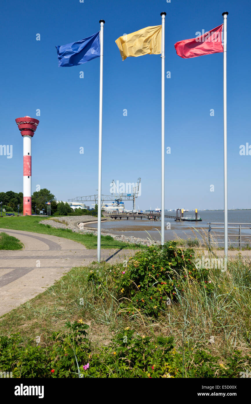 Nordenham, lighthouse and harbor on the Weser river, flagpoles in foreground - Stock Image