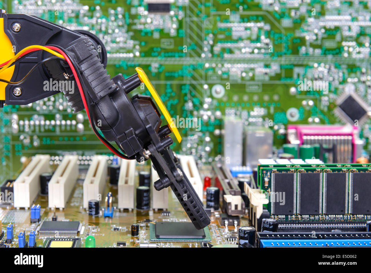 Robotic arm installing a computer chip - Stock Image