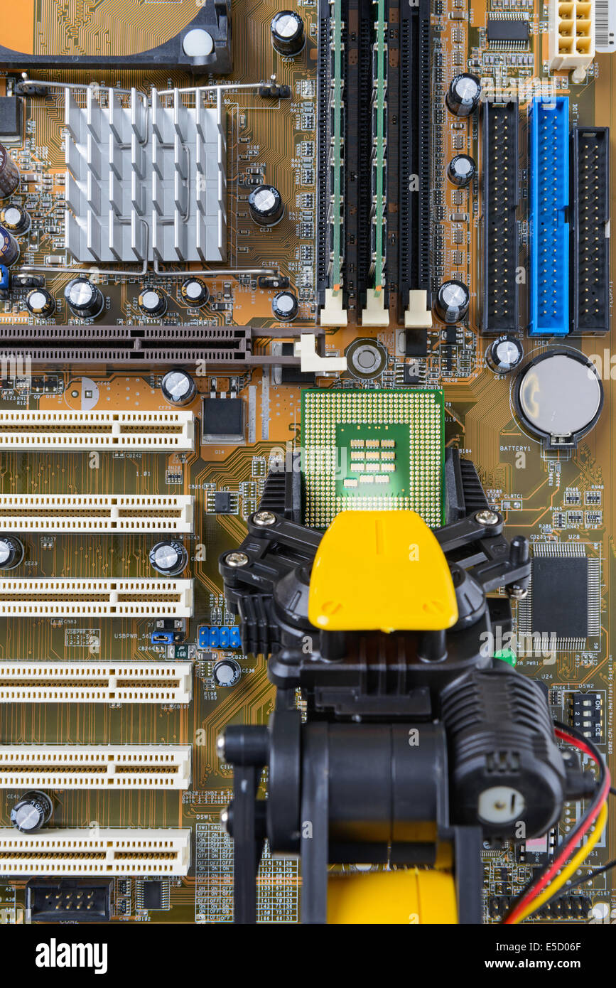 Robotic arm installing a computer chip on a motherboard. - Stock Image