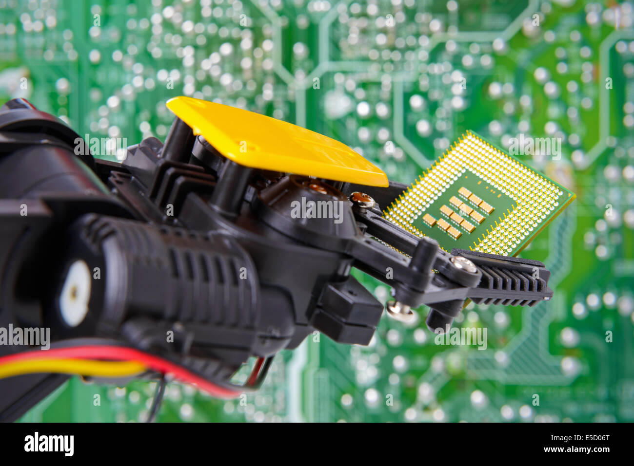 Robotic arm holding a computer chip against a circuit board background. - Stock Image