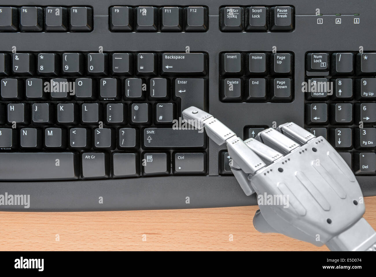 Robot hand typing on a computer keyboard. - Stock Image