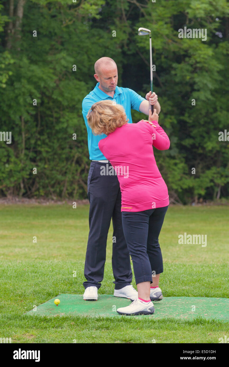 A lady golfer being taught to play golf by a Pro on a practise driving range. - Stock Image