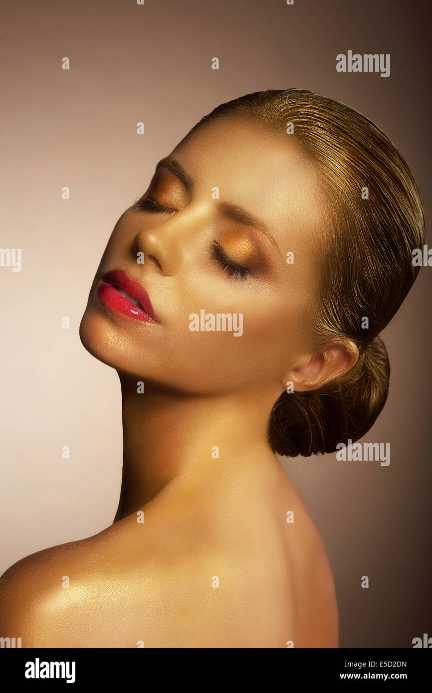 Artistry. Fanciful Bronzed Woman's Face. Futuristic Art Gold Makeup - Stock Image