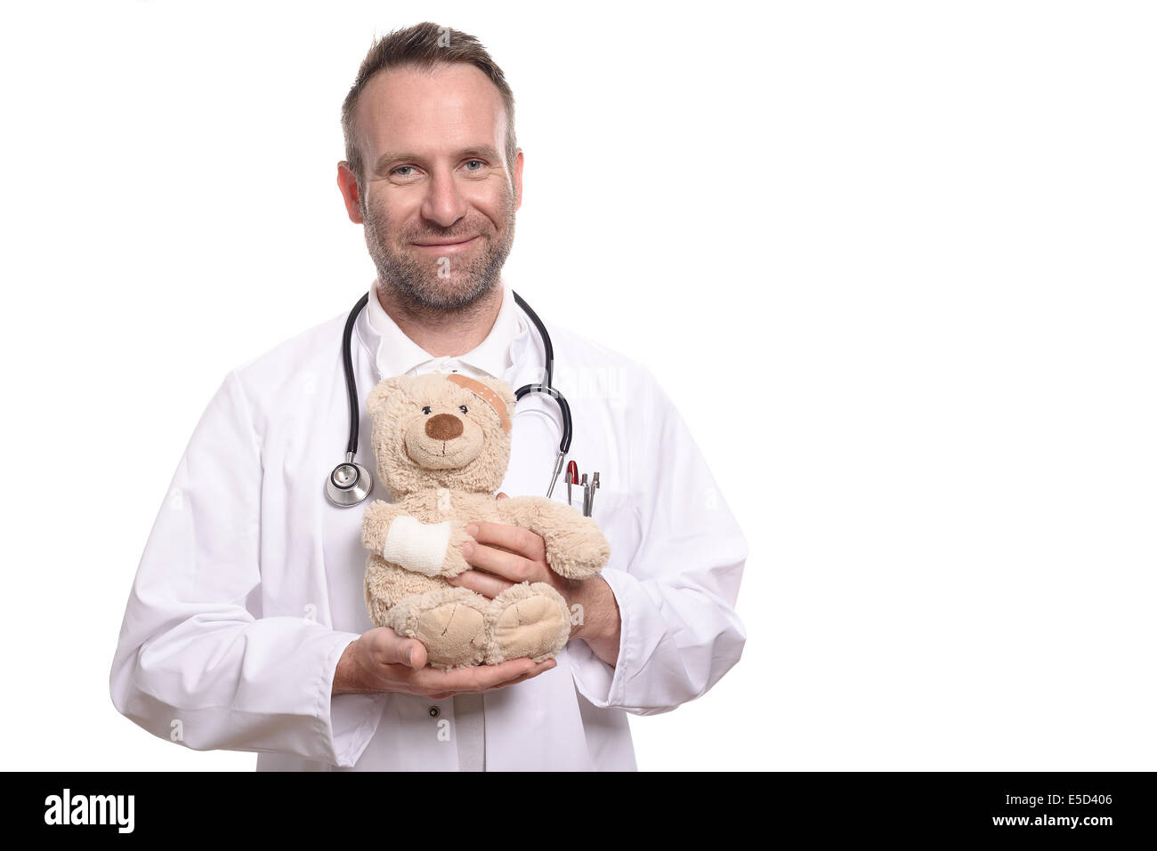 Friendly smiling middle-aged male pediatrician with unshaven stubble holding a teddy bear with a bandaged arm to - Stock Image