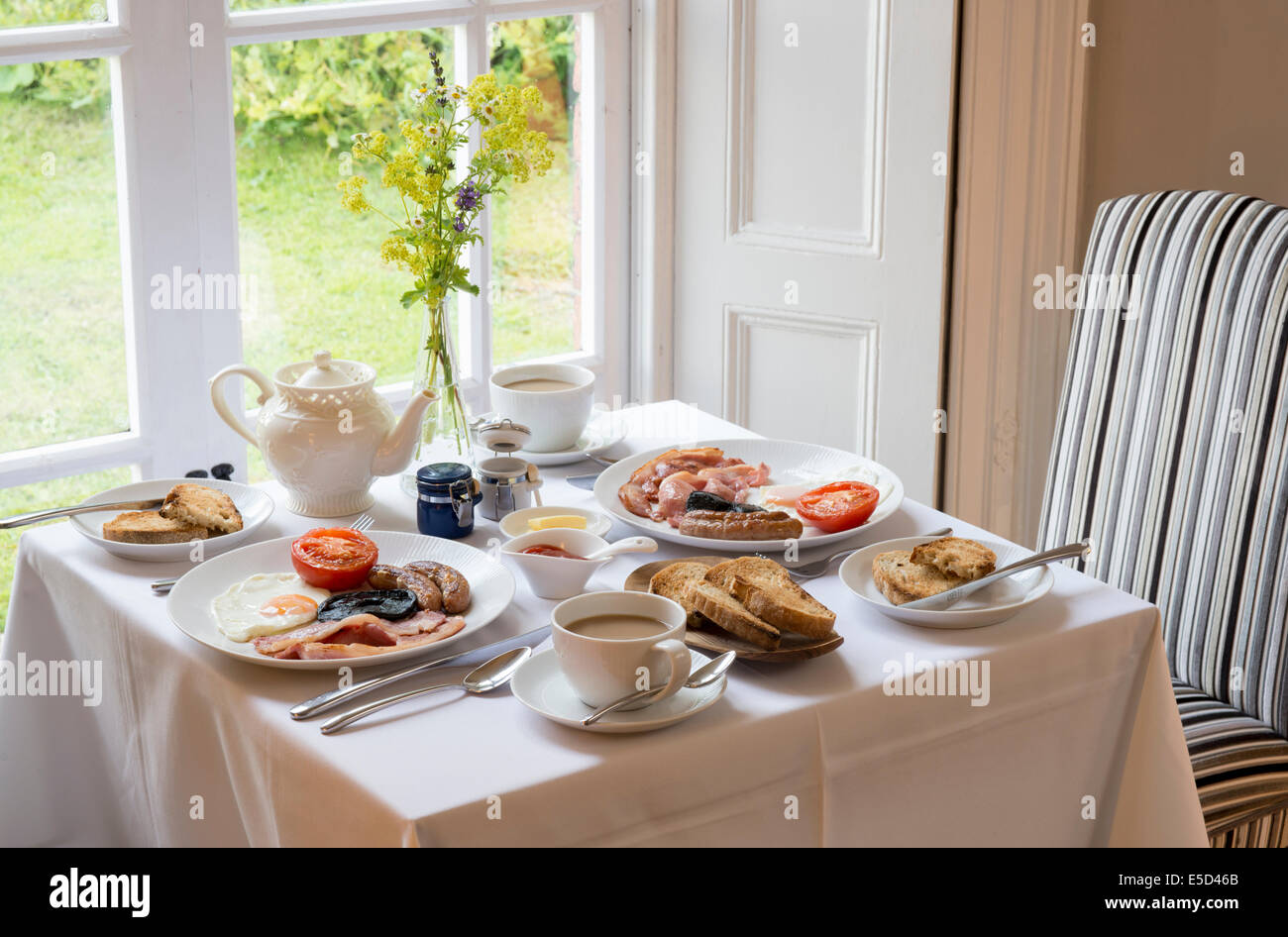 Traditional English Breakfast table laid out by window room interior with tea toasts bacon sausage and egg on tablecloth & Traditional English Breakfast table laid out by window room interior ...