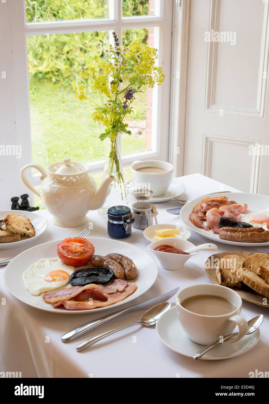Traditional English Breakfast table laid out by window room interior with tea toasts bacon sausage and egg on tablecloth - Stock Image