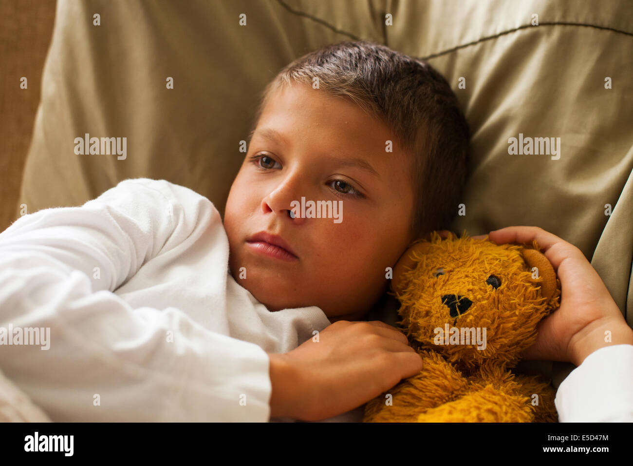 child feeling sick in bed - Stock Image
