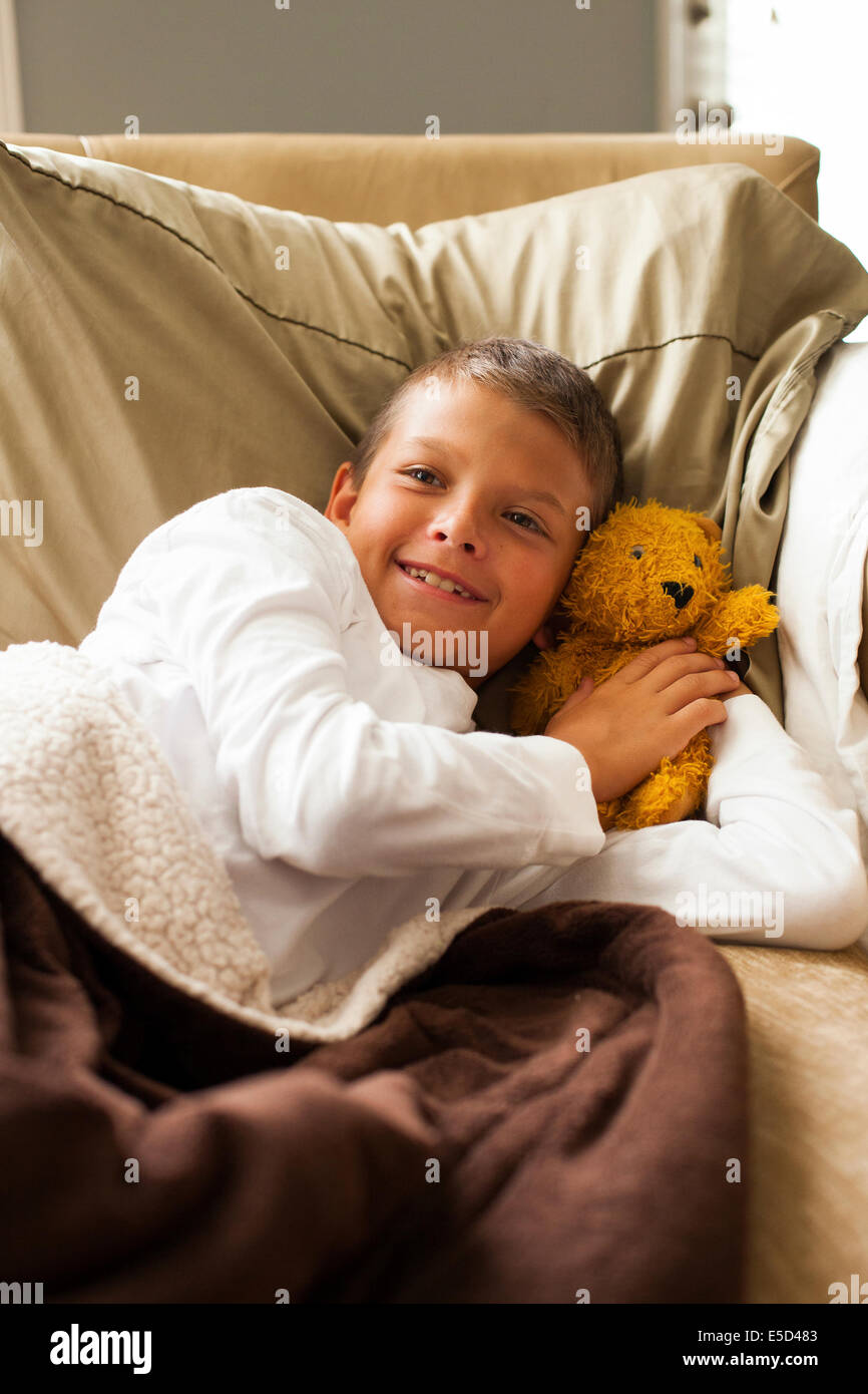 Boy resting on bed with teddy - Stock Image