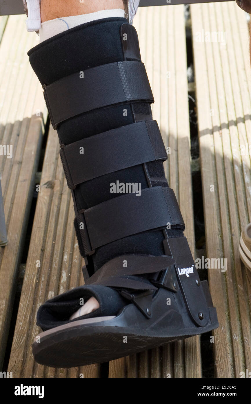 Mans leg encased in a medical walking boot after an Achilles heel Operation - Stock Image