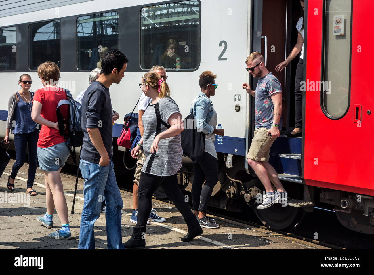 Passengers and commuters boarding passenger train on platform in railroad station - Stock Image
