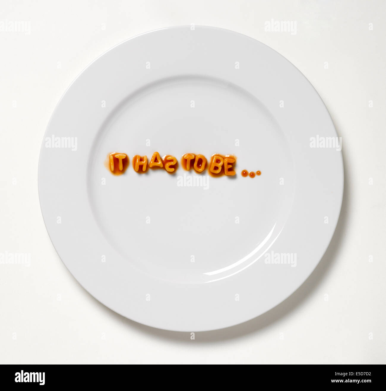 A white plate with the word ' it has to be' made up from pasta shapes - Stock Image