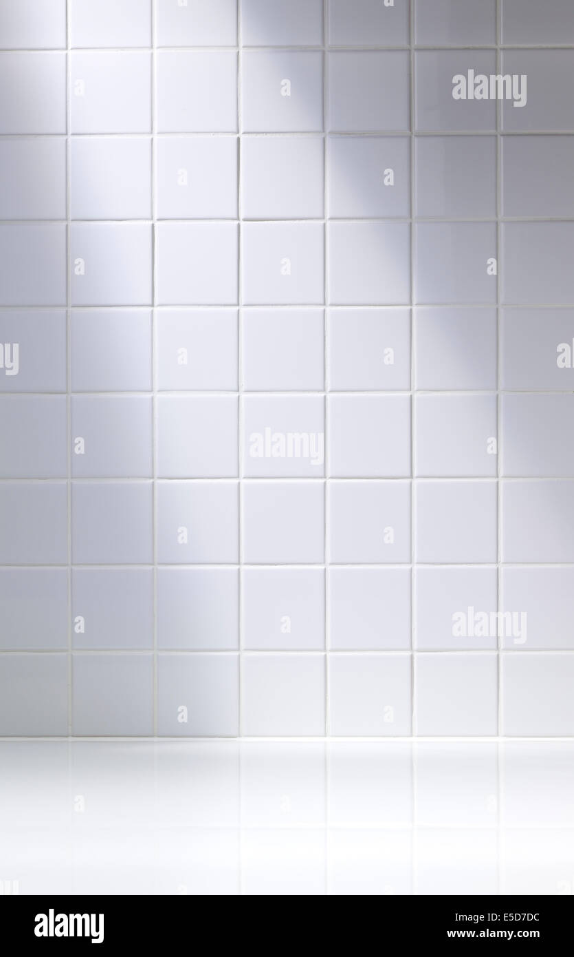 A vertical shot of a white tiled background or bathroom - Stock Image