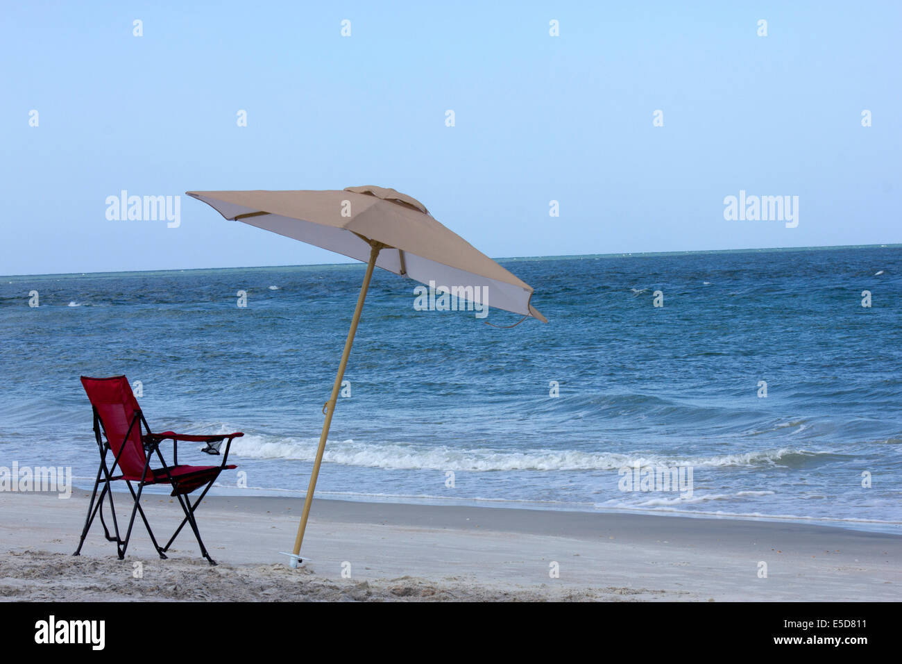 Chair and Umbrella at the Vilano beach, over the Atlantic Ocean, at the mouth of the river Matanzas, in a  hot summer, - Stock Image