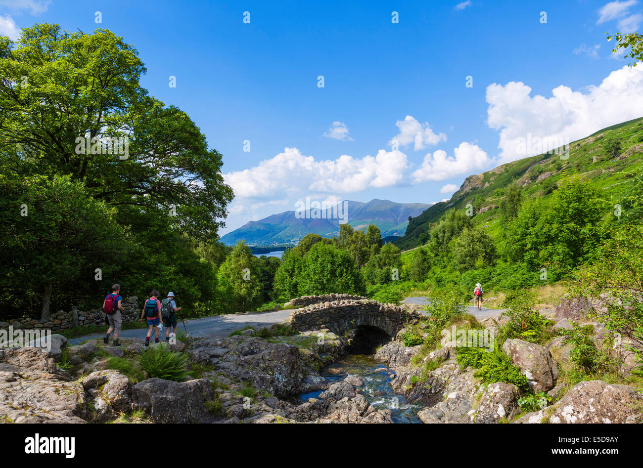 Walkers at Ashness Bridge with Skiddaw massif in the distance, Borrowdale, Lake District, England, UK - Stock Image