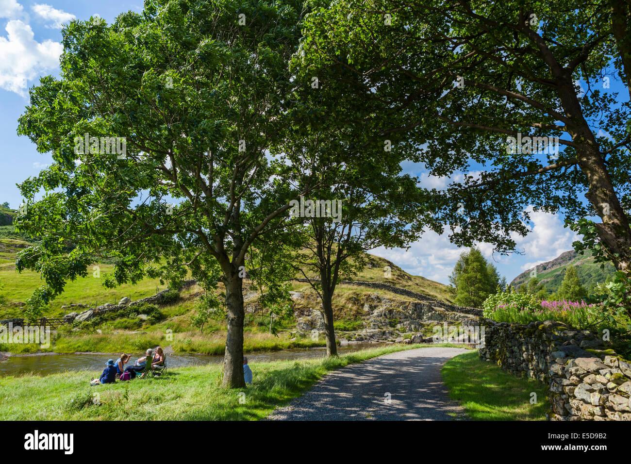 People picnicking by the side of Watendlath Beck, Watendlath Tarn, Borrowdale, Lake District, England, UK - Stock Image