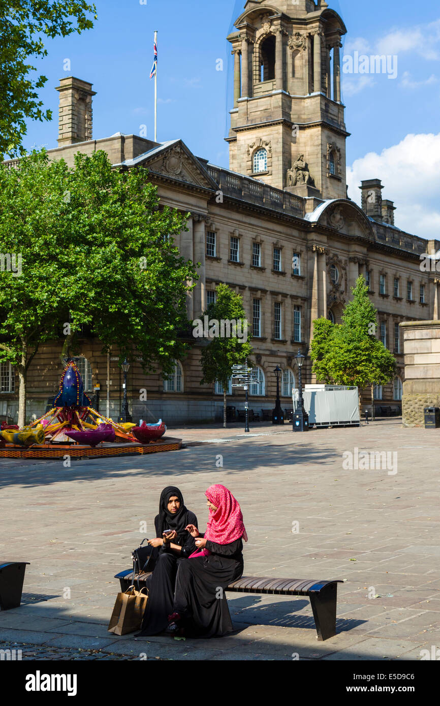 Two young muslim girls in traditional dress sitting in front of the Town Hall, Market Square, Preston, Lancashire, - Stock Image