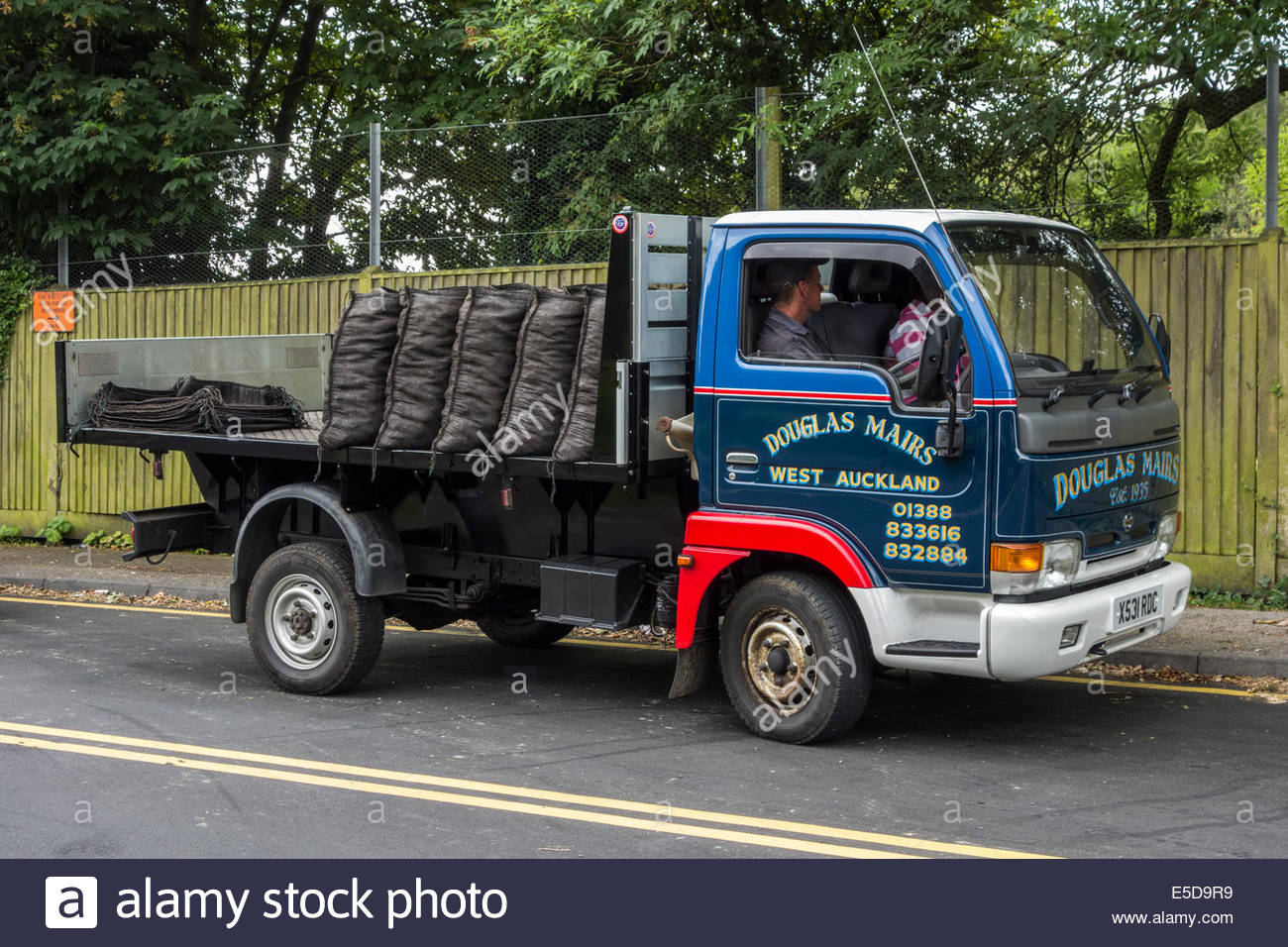Coal lorry with full and empty sacks on the back - Stock Image