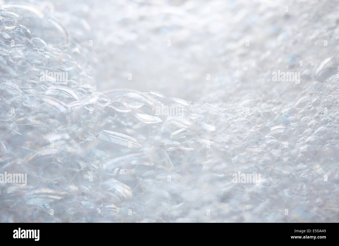 A close up of fluffy white bath bubbles (soap suds). Short depth of field. No people. - Stock Image