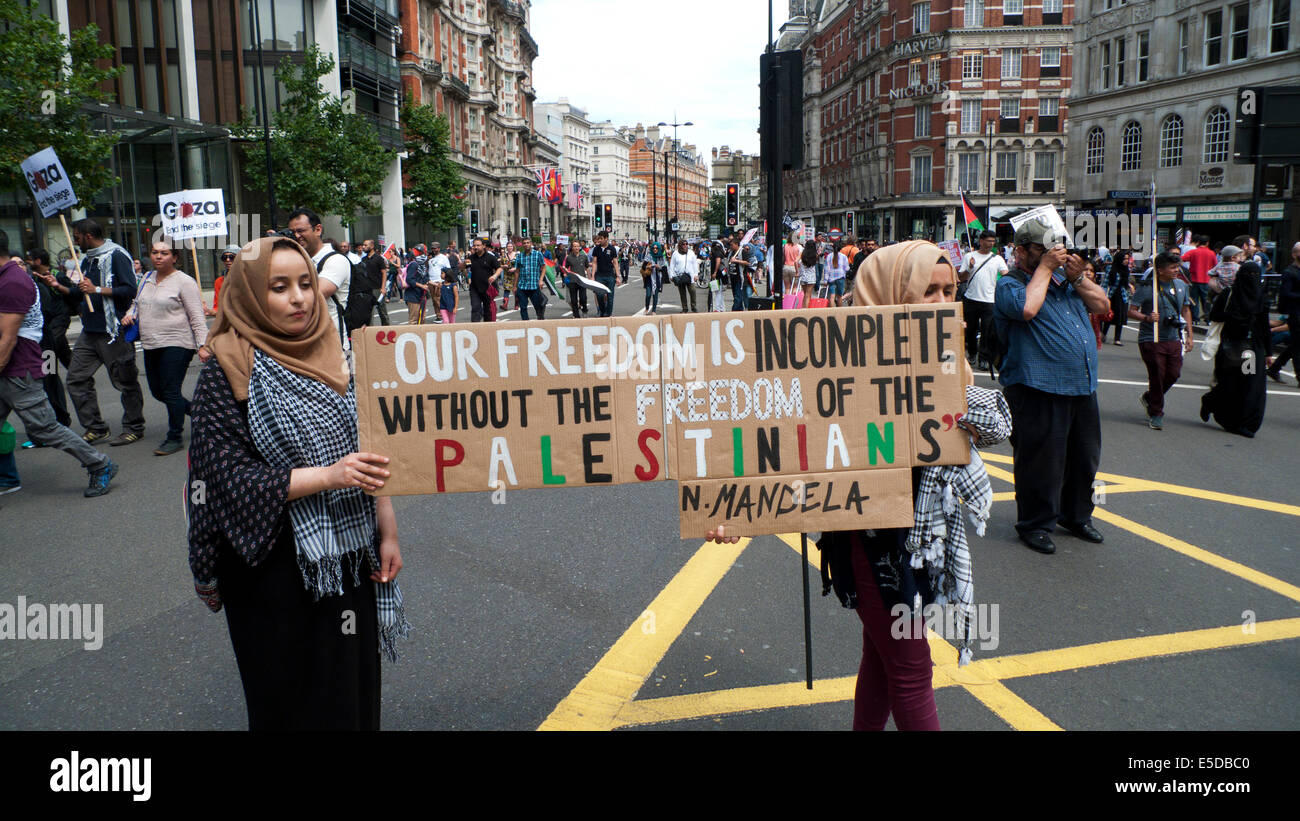 Protesters protestors protest demonstration on the streets of London UK against bombing of Gaza Palestinians by - Stock Image