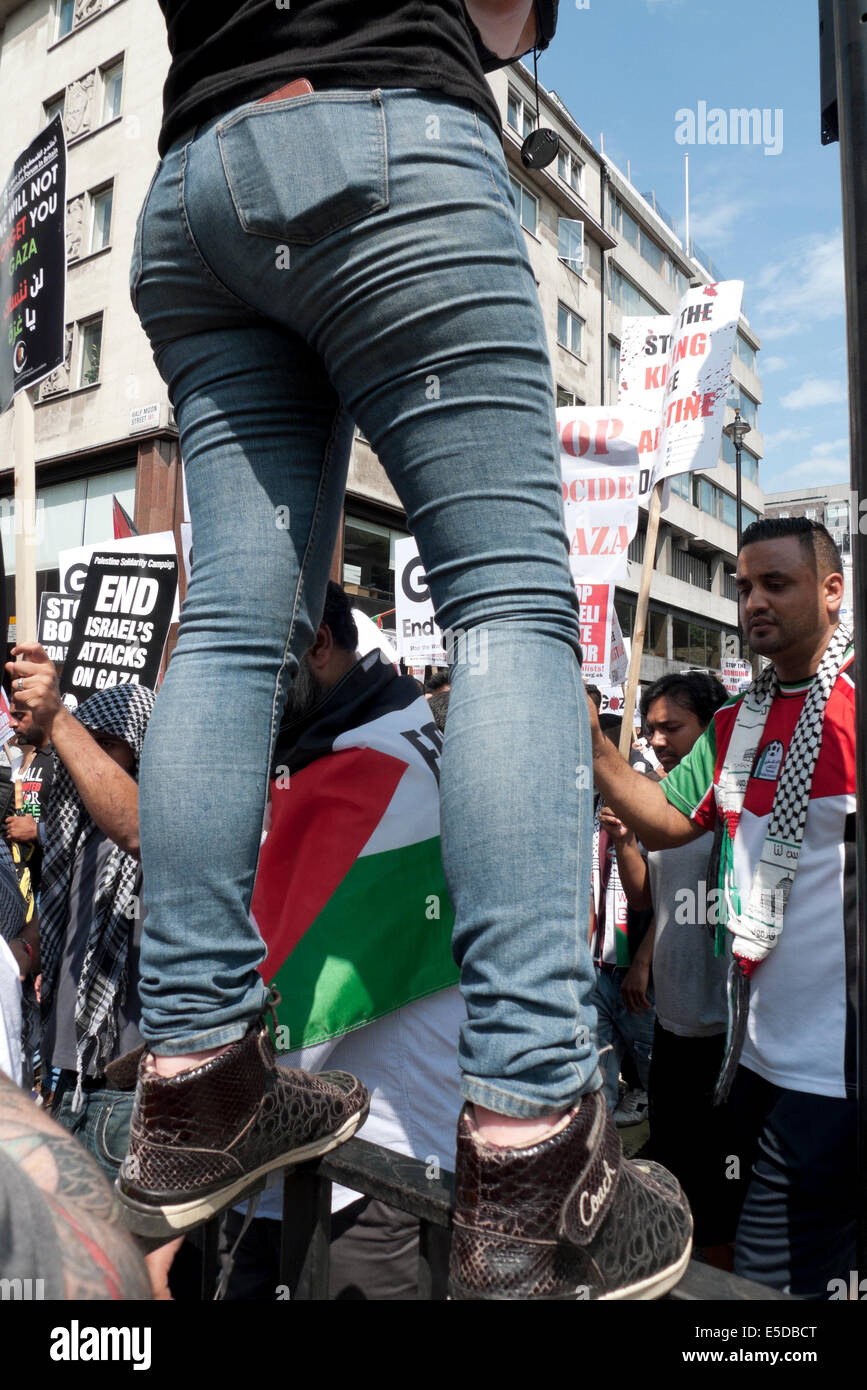 Woman photographing demo on the streets of London UK against bombing of Gaza Palestinians by Israel  19.7.2014  - Stock Image