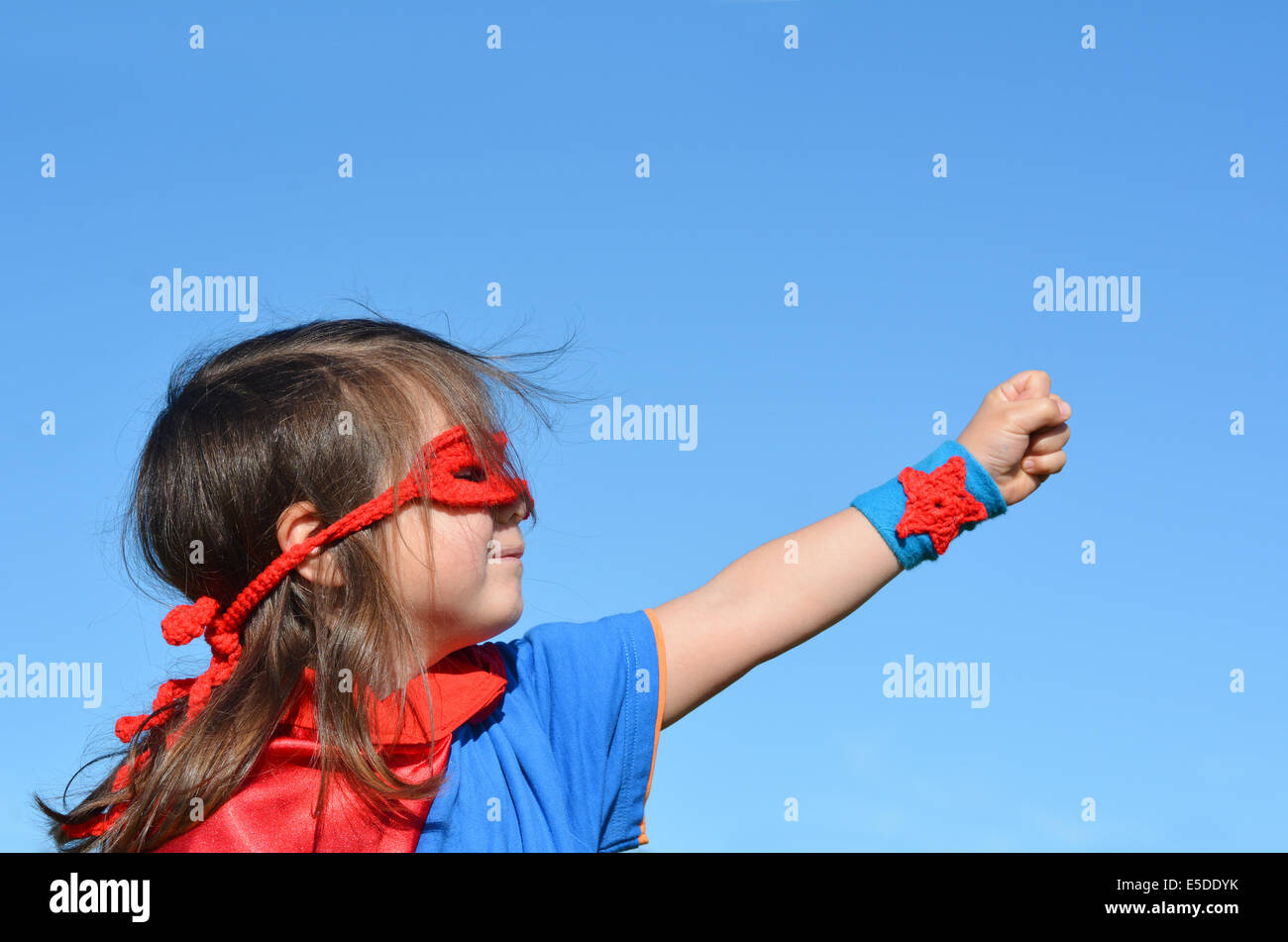 Superhero child (girl) against dramatic blue sky background with copy space. concept photo of Super hero, girl power, - Stock Image