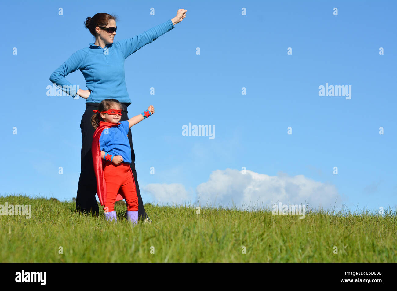 Superhero mother and daughter against dramatic blue sky background with copy space. concept photo of Super hero, - Stock Image