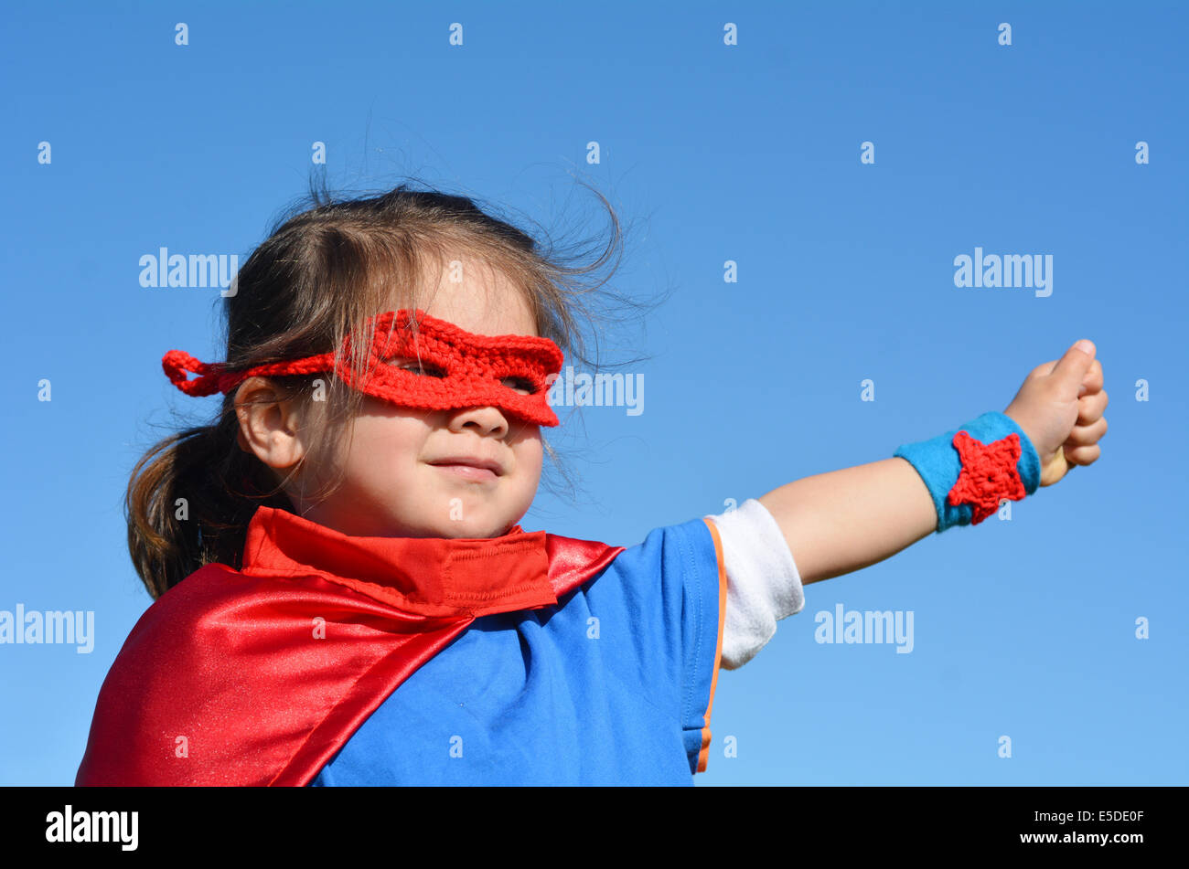Superhero child (girl)  against dramatic blue sky background with copy space. concept photo of Super hero, girl - Stock Image