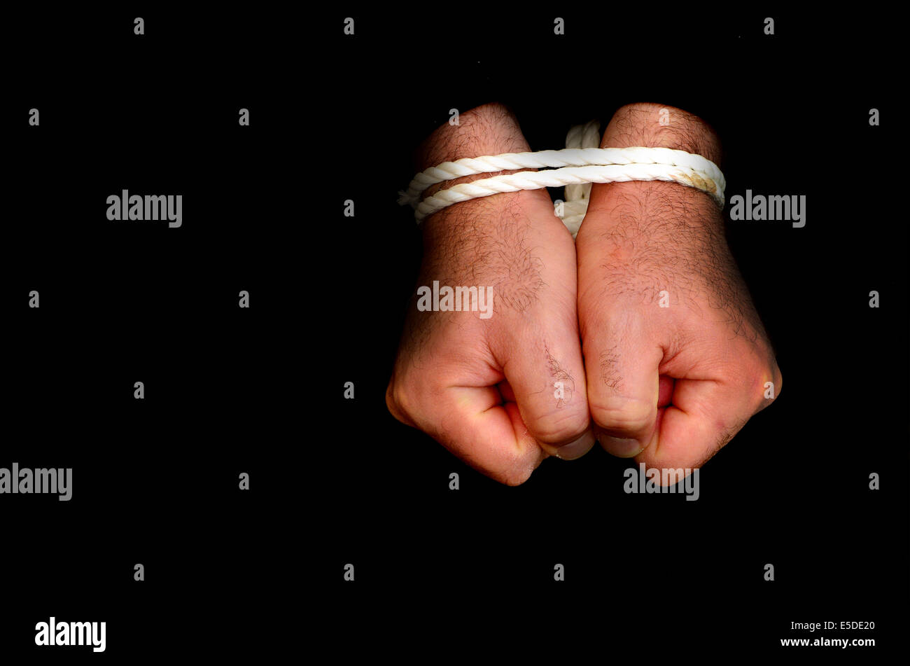 Hands of a missing kidnapped, abused, hostage, victim man  tied up with rope in emotional stress and pain, afraid, - Stock Image
