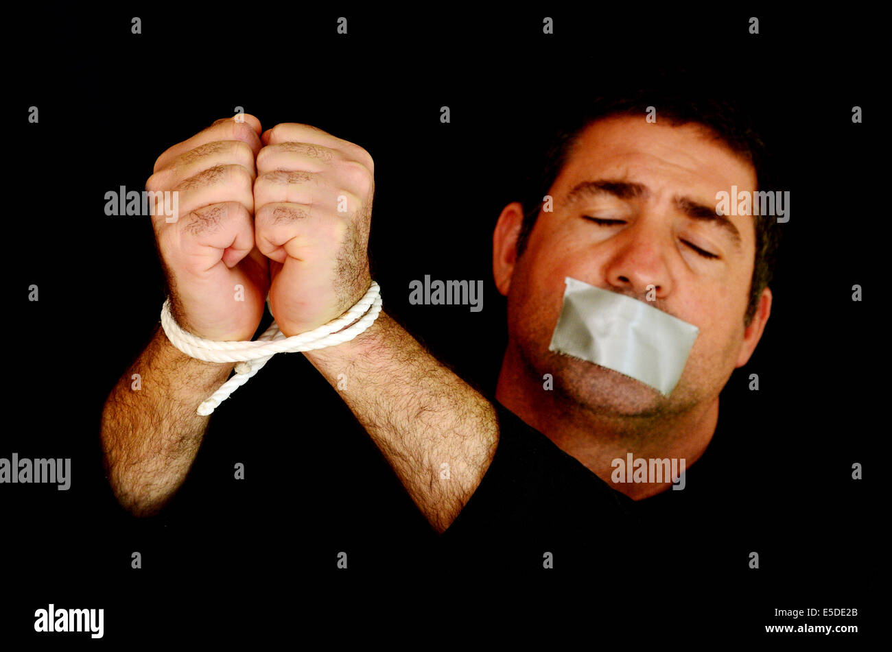Missing kidnapped, abused, hostage, victim man with hands tied up with rope in emotional stress and pain, afraid, - Stock Image