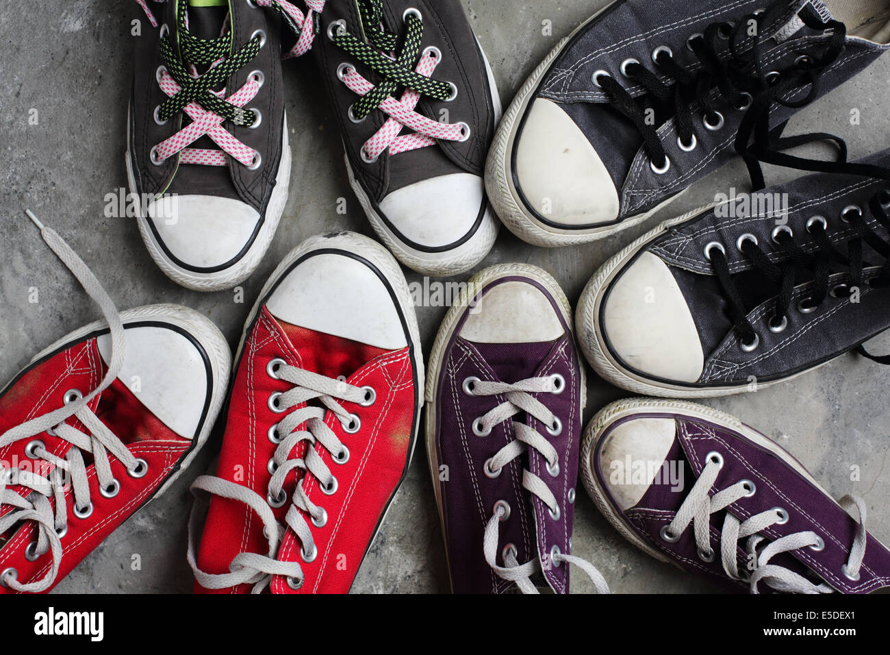 Four pairs of Converse shoes shot against a concrete background - Stock Image