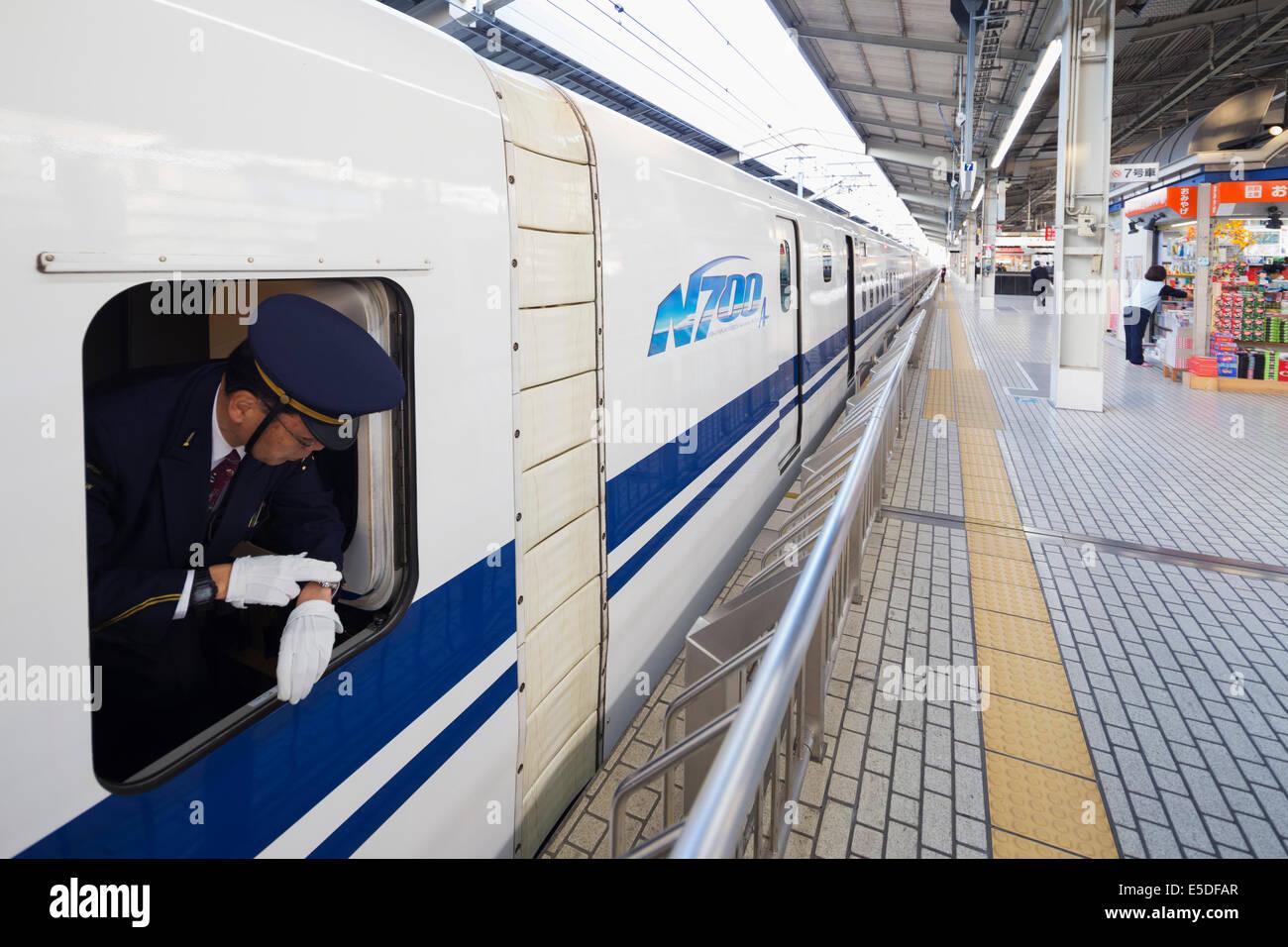 Asia, Japan, Honshu, shinkansen bullet train, conductor time keeping departure - Stock Image