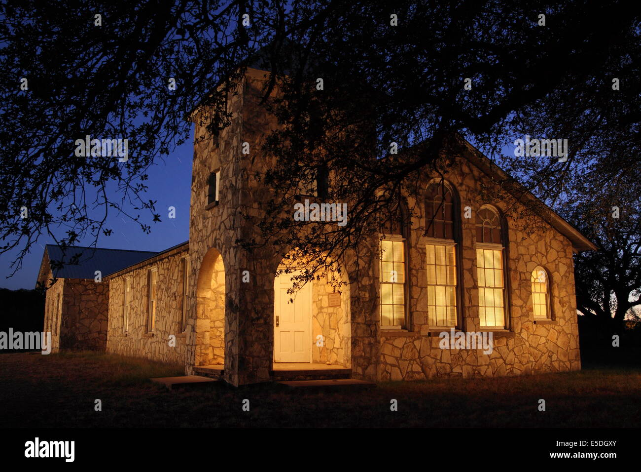 A light-painting of Roosevelt Church among oak trees, near Junction, Texas. - Stock Image