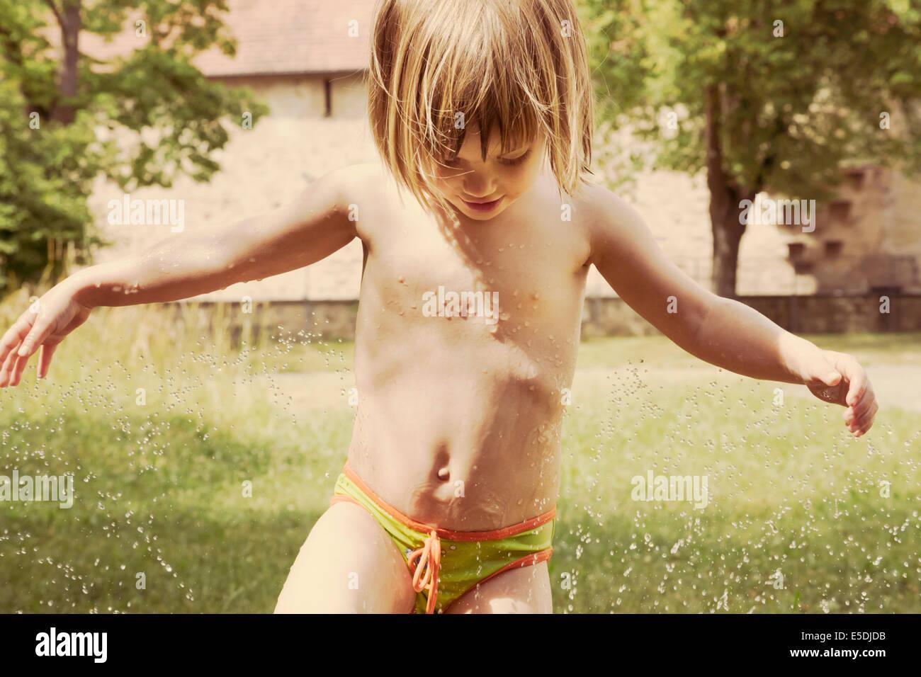 Portrait of little girl having fun with lawn sprinkler in the garten - Stock Image
