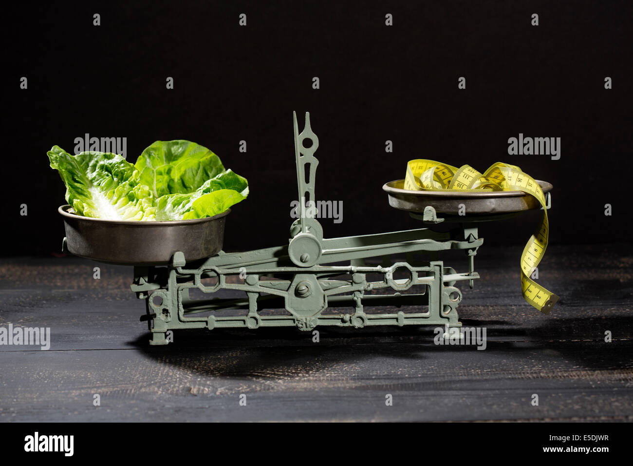 Lettuce leaves and tape measure on scale - Stock Image