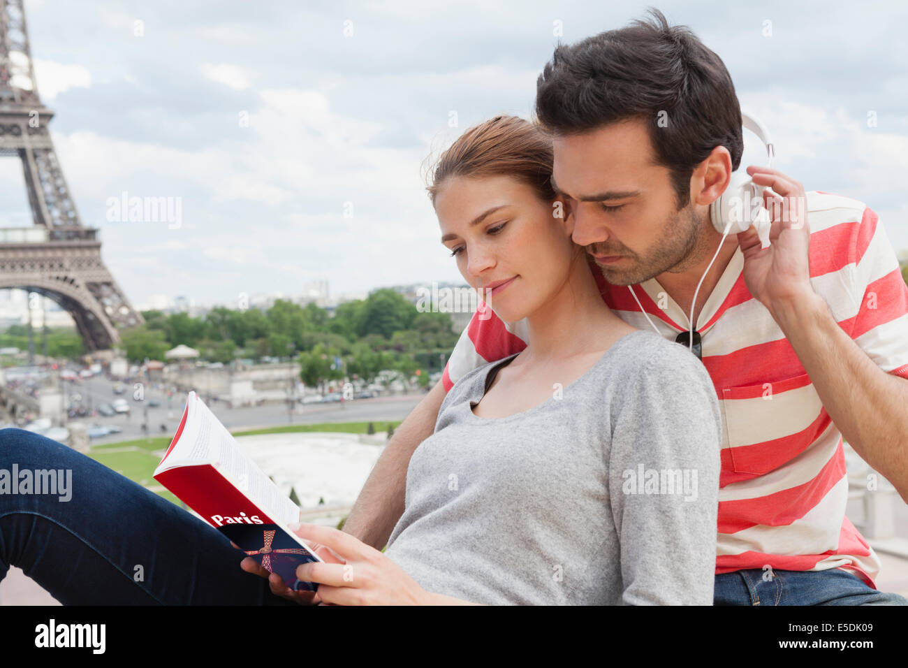 France, Paris, portrait of couple with travel guide and headphones in front of Eiffel Tower - Stock Image