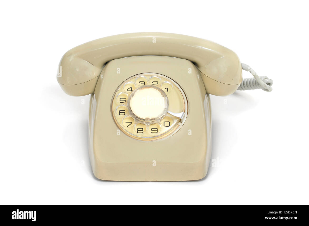 a beige old rotary dial telephone on a white background - Stock Image